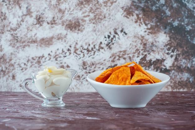 大理石のテーブルの上に、ボウルにスパイシーなポテトチップスを入れ、グラスにヨーグルトを入れます。