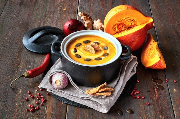 Spicy pumpkin creme soup with ginger, spanish onion, garlic and chili in ceramic pan on dark wood