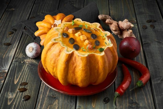 Spicy pumpkin soup served in a hollowed pumpkin on dark wood with ingredients
