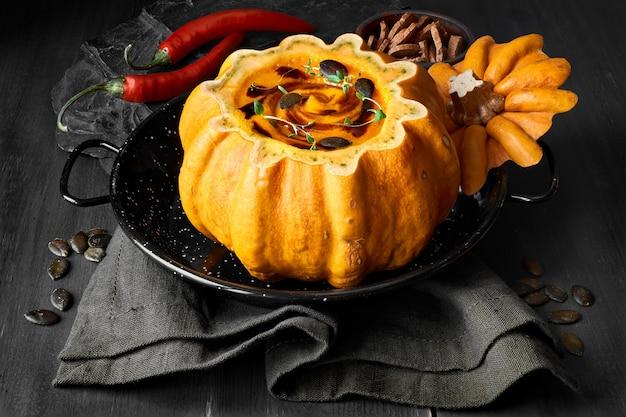 Spicy pumpkin soup served in a hollowed pumpkin on dark wood