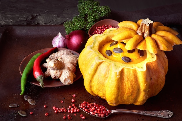 Spicy pumpkin soup served in a hollowed pumpkin on dark