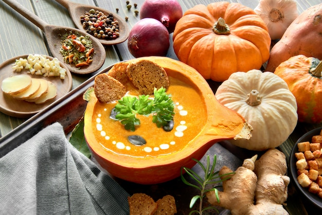 Spicy pumpkin soup served in a hollowed pumpkin with ingredients and text space