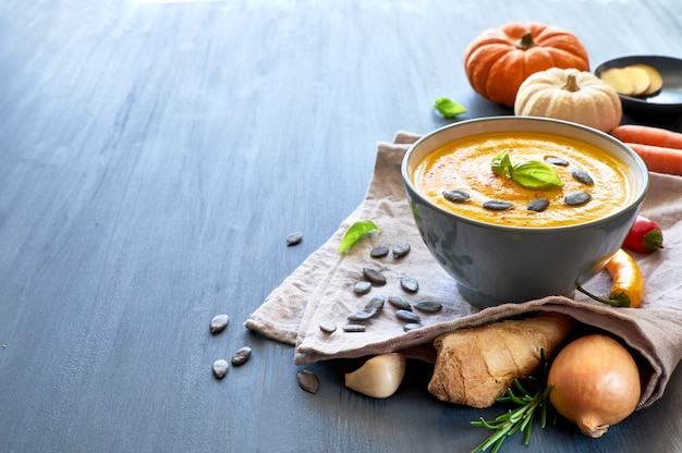 Spicy pumpkin soup with ginger, served with basil, pumpkin seeds and dried chil