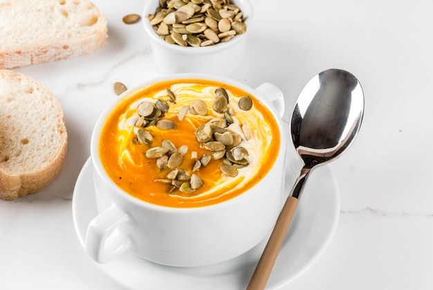 Spicy pumpkin soup with pumpkin seeds, cream and freshly baked baguette on black stone table