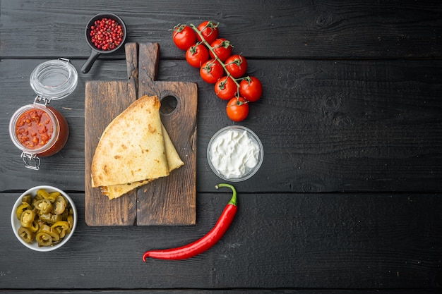 Spicy quesadilla made of tortilla with sauce and herbs, on black wooden table background, top view flat lay  with copy space for text
