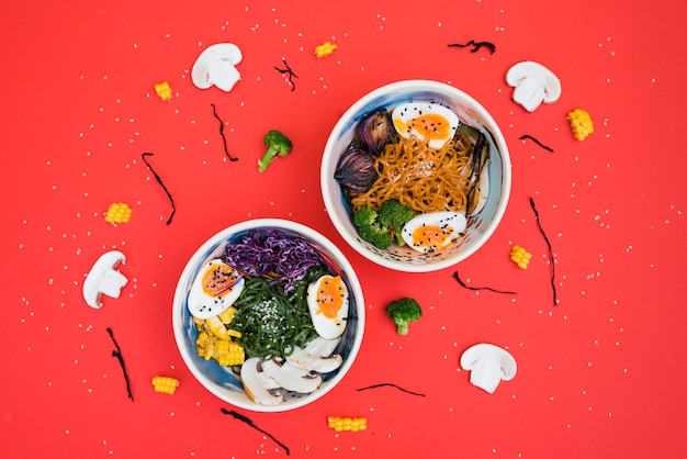 Spicy ramen bowls with noodles; boiled egg and vegetables served with seaweed salad on red backdrop