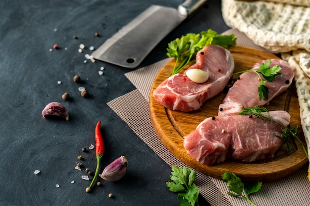 Spicy raw meat on a wooden slicing or cutting board, put a salt on an uncooked meats