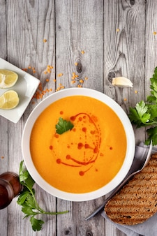 Spicy red lentil soup on gray wooden table