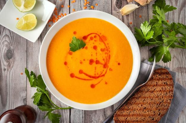 灰色の木製のテーブルにスパイシーな赤レンズ豆のスープ