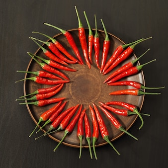 Spicy red peppers spread out in a circle on the clay flat dis