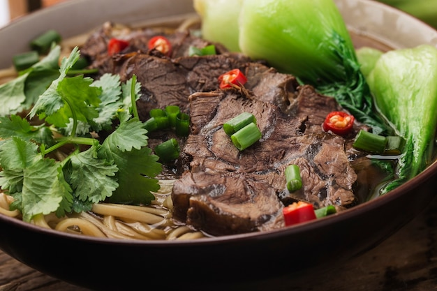 Spicy red soup beef noodle in a bowl on wooden table