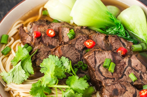 나무 테이블에 그릇에 매운 빨간 수프 쇠고기 국수