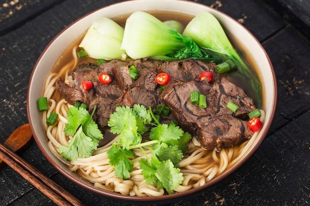 木製のテーブルのボウルにスパイシーな赤いスープ牛肉麺