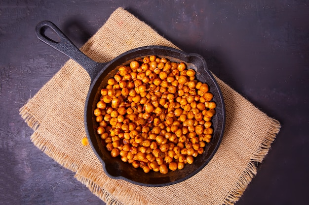 黒い金属鍋にスパイシーなローストひよこ豆。健康的なベジタリアン料理。
