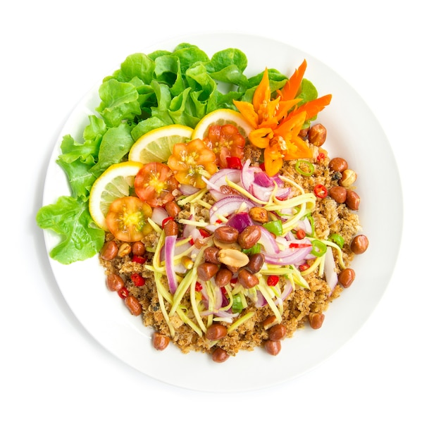 Spicy salad crispy catfish with mango slice hot tasty food of thai on top fried peanuts decorate with green oak chili carved and lemon top view isolated on white background