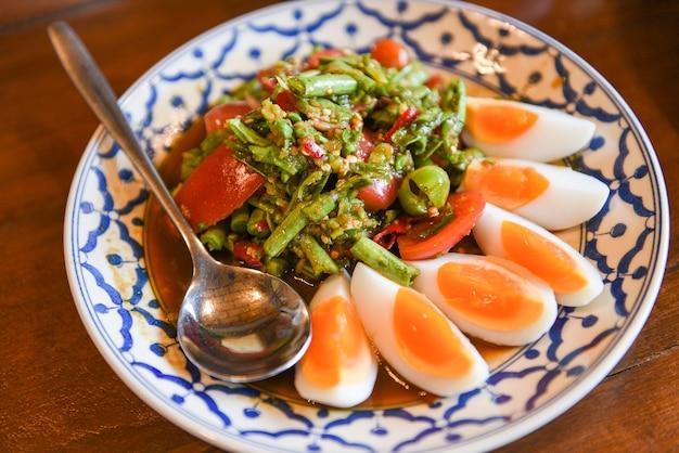 Острый салат, вареные яйца из длинной фасоли на тарелке тайская еда
