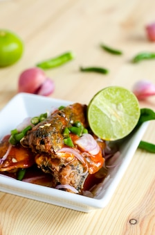 나무 테이블에 통조림 정어리 생선 매운 샐러드