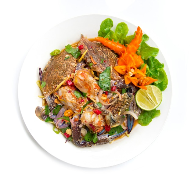 青いカニのスパイシーサラダタイのスパイシーな料理の前菜タイ料理の美味しさを飾る白い背景に分離された唐辛子彫刻上面図