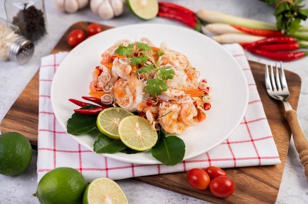 Острый салат с креветками на белой тарелке. тайская еда.