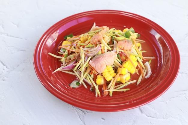 Острый салат с лососем на мраморном столе в ресторане, тайская еда, овощной и рыбный лосось, хорошая еда для здоровья, thai call yum (салат и острый)