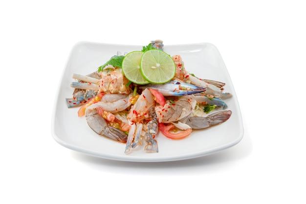 白で隔離スパイシーなシーフードサラダ、新鮮なエビと青カニ、タイ料理のパパイヤサラダ
