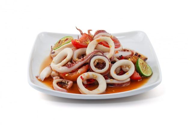 Пряный салат из морепродуктов с кальмарами на белой стене.