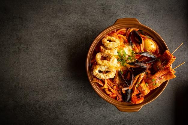Острый суп из морепродуктов кладут на тарелку