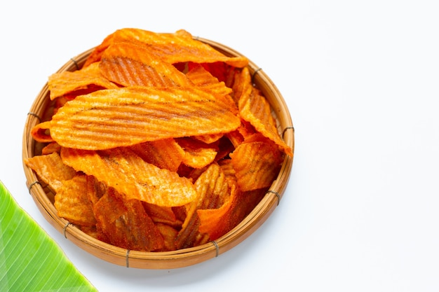 Spicy snack, banana slice chips paprika flavor in bamboo basket on white background.