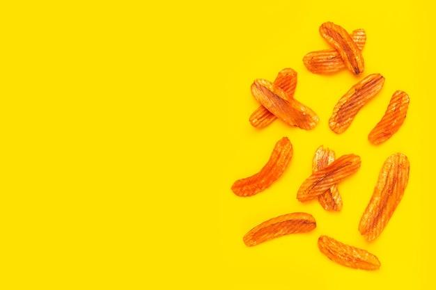 매운 스낵, 노란색 배경에 바나나 슬라이스 칩 파프리카 맛.