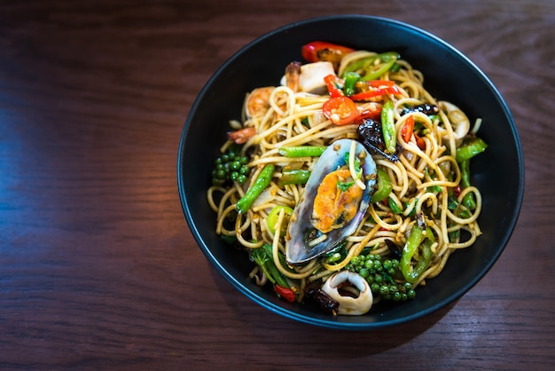 Spicy spaghetti with seafood in black dish on wooden table, top view