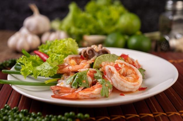 Острый салат из кальмаров и креветок в белом блюде с лимонной кинзой и листьями салата