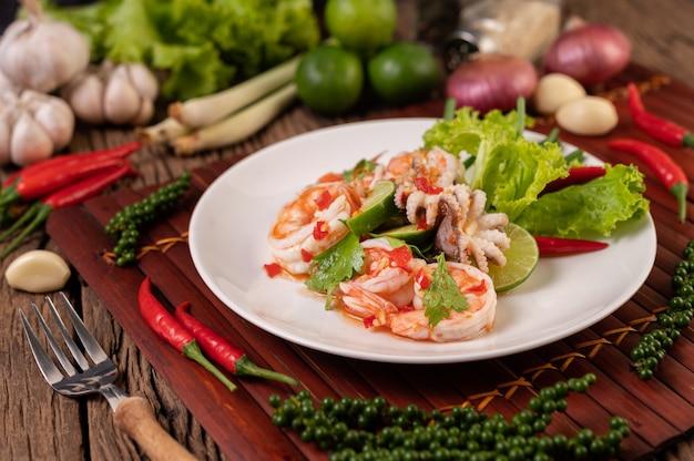 レモンコリアンダーとレタスを添えた白皿のスパイシーなイカとエビのサラダ