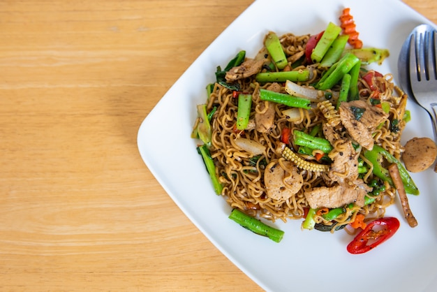 Spicy stir fried instant noodle and holy basil leaves on wooden table