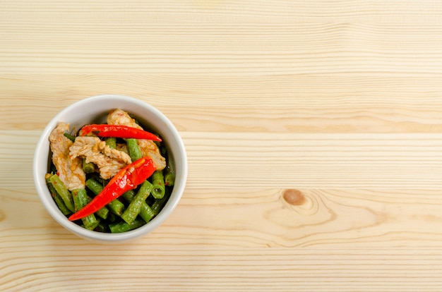 Spicy stir fried pork with red curry paste and yard long bean, thai food menu