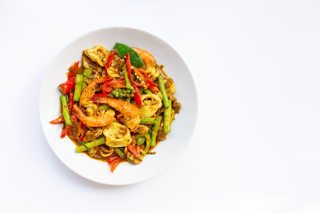 Spicy stir fried shimp, squid and pork with thai southern chili paste and longbean on white background.