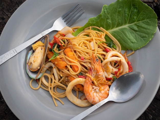 Spicy stir fried spaghetti seafood in white bowl. top view