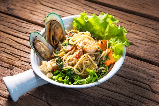 Spicy stir fried spaghetti with seafood, put in a beautiful terracotta cup, put on a wooden table.