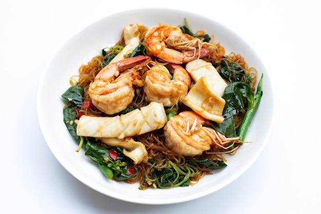 Жареная вермишель с пряностями, листья базилика, морепродукты, креветки и кальмары