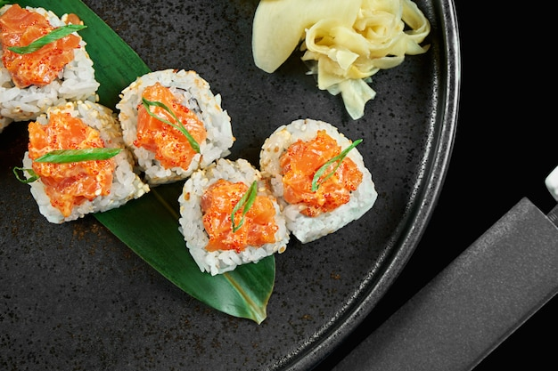 Spicy sushi rolls with rice, norms, mayonnaise, tobiko caviar and salmon on a black ceramic plate on a black surface. japanese traditional food.