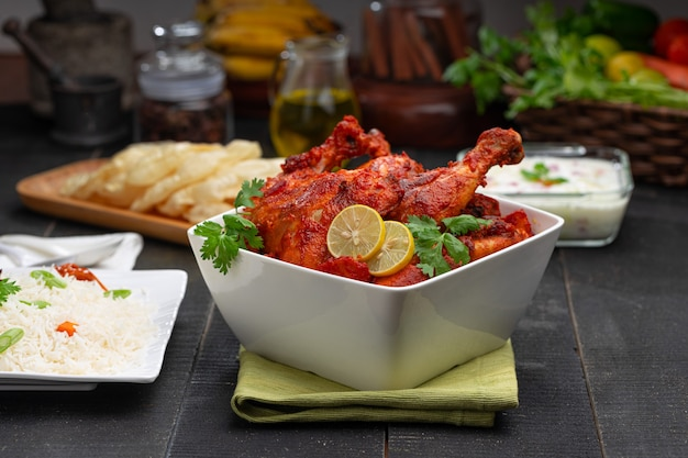 정사각형 모양의 흰색 그릇에 고수 잎으로 장식한 매운 탄두리 치킨