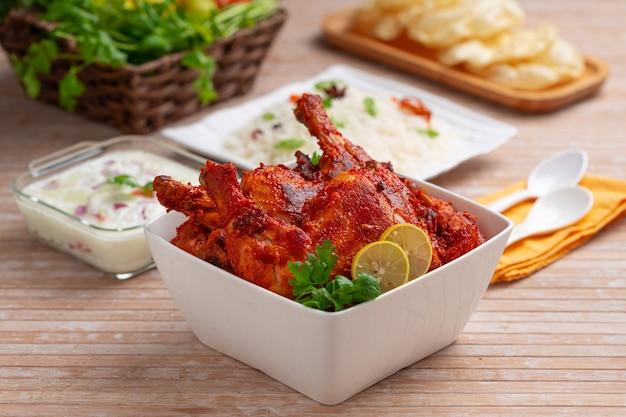 Spicy tandoori chicken garnished with coriander leaf in square shaped white bowl