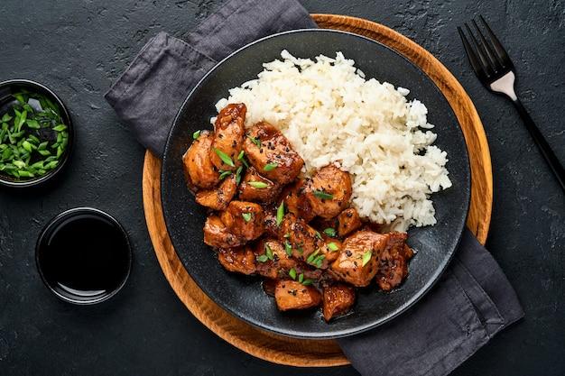 Острые кусочки куриного филе терияки с рисом, зеленым луком и черным кунжутом на черной тарелке на темном сланцевом, каменном или бетонном фоне. вид сверху с копией пространства.