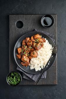 Острые кусочки куриного филе терияки с рисом, зеленым луком и черным кунжутом на черной тарелке