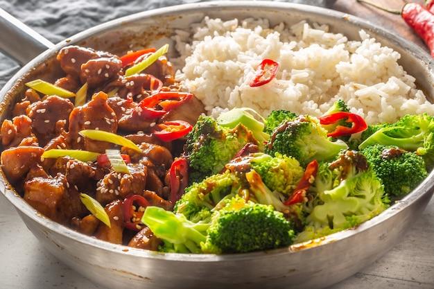 ブロッコリーとご飯を鍋に入れて蒸したスパイシーな照り焼きチキン。