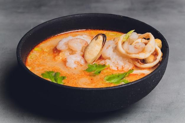 매운 태국 수프 톰 얌 코코넛 밀크, 칠리 페퍼 및 해산물 새우와 연어 검정색 배경에 접시에. 아시아 요리, 레스토랑 메뉴.