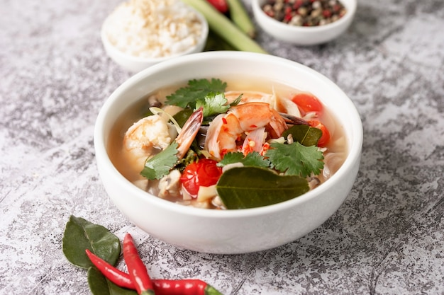 Spicy tom yam kung, tom yum sour soup with shrimp, prawn, coconut milk, lemongrass and chili pepper in a bowl