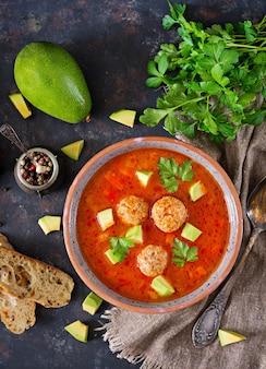 Острый томатный суп с фрикадельками и овощами. подается с авокадо и петрушкой. здоровый ужин. плоская укладка.