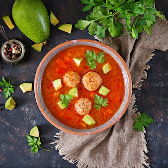 Spicy tomato soup with meatballs and vegetables. served with avocado and parsley. healthy dinner.flat lay. top view