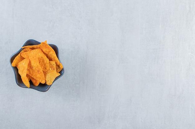Spicy tortilla chips in dark bowl on stone.
