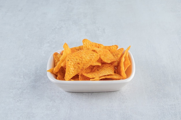 Spicy triangle chips in white bowl on stone.